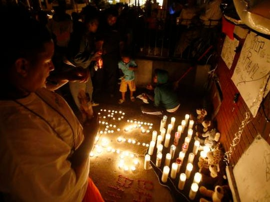 "Mourners arrange candles to write ""RIP BAM"" - the nickname of the man shot by police Wednesday – during a gathering in front of his mother's home Thursday night."
