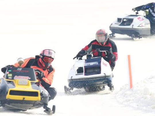 A class of vintage snowmobiles compete during Saturday's