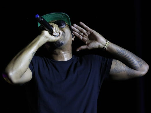 Rapper Nas holds the mic up to the crowd Friday, July