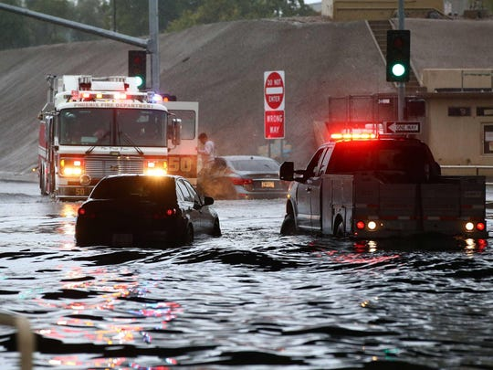 Floodwaters strand several cars on Greenway Road at the Interstate 17 underpass in Phoenix.
