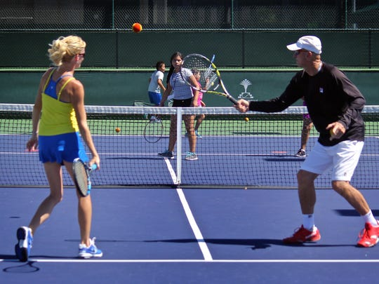 Camp tennis coach Tom Fey, right, and another instructor play tennis with a group of children Thursday at the Indian Wells Tennis Garden. About 50 East Valley kids had the opportunity to improve their tennis skills by learning from pros Rosie Casals and Tory Fretz.