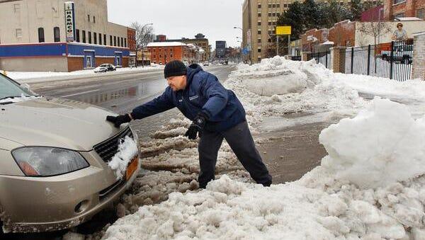 Edwin Ramos helps a car out of a snow bank Sunday.