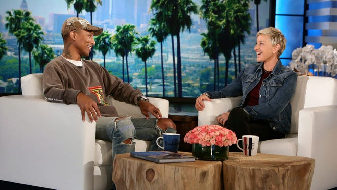 """In this photo released by Warner Bros., host Ellen Degeneres speaks with singer and film producer Pharrell Williams during a taping of """"The Ellen DeGeneres Show"""" at the Warner Bros. lot in Burbank, Calif. Williams appeared as scheduled on Thursday's show without fellow singer Kim Burrell, who was disinvited days earlier after she referred to gays and lesbians as perverted.  (Photo by Michael Rozman/Warner Bros.)"""