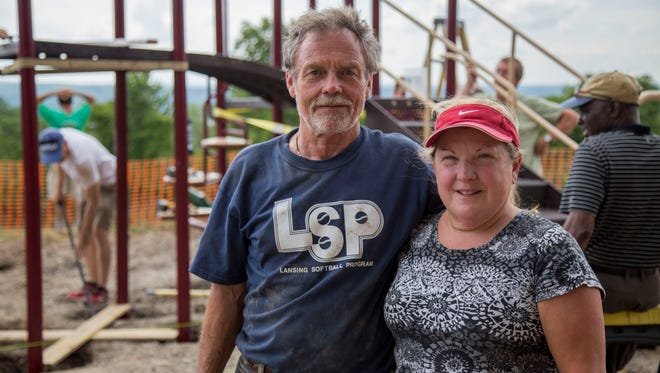Wayne and Marcia Larsen stand in front of a playground dedicated to their son, Brent, at the Lansing United Methodist Church. Brent died two years ago of Duchenne Muscular Dystrophy.