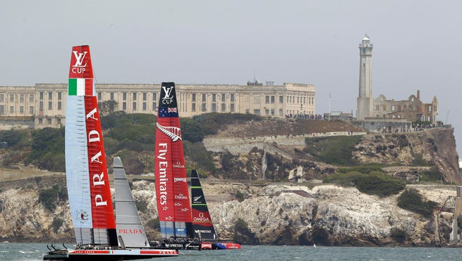 Luna Rossa Challenge, left, of Italy and Emirates Team New Zealand, right, pass Alcatraz Island during the second race of their America's Cup challenger series final sailing event Sunday in San Francisco. Luna Rossa Challenge won the race to even their series after Emirates Team New Zealand fell out of the race because of a mechanical problem.