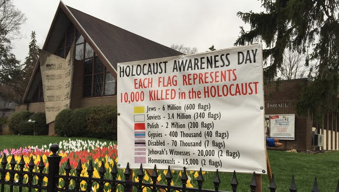 A banner honoring the millions killed by the Nazis in the Holocaust is back in place in front of Congregation Sons of Israel in Upper Nyack Friday, April 17, 2015, a day after it was found torn apart.