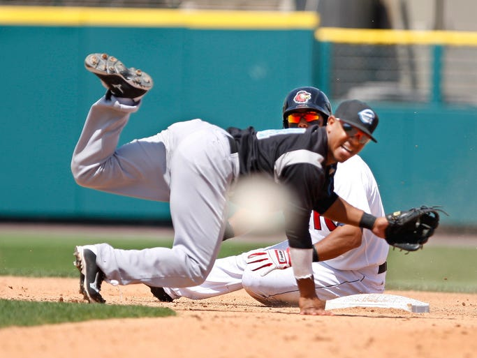 Rochester's Wilkin Ramirez slides hard into second base breaking up a double play as Syracuse second baseman Josh Johnson sends the relay throw into the dugout during the fourth inning.  Wings' Brad Nelson scored on the play.