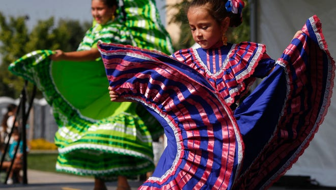 Kaiya Reinders, 6, of Des Moines, right, and Diana Bombadillo, 11, of Des Moines perform a dance during the 2016 Latino Heritage Festival on Saturday, Sept. 24, 2016, at Western Gateway Park in Des Moines.