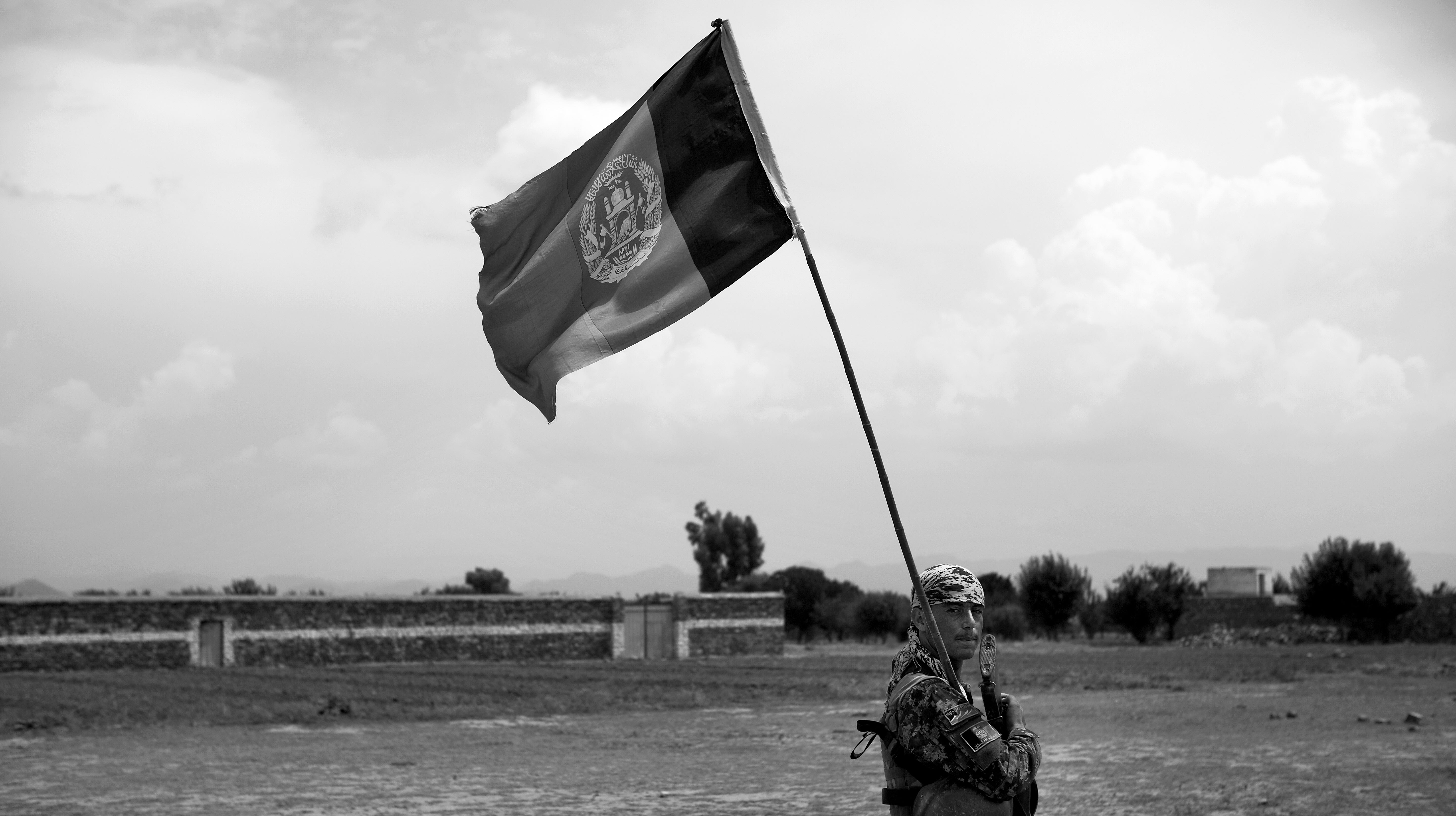 An Afghan National Army soldier carries a flag on a patrol.