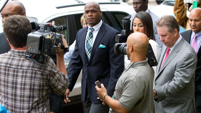 Minnesota Vikings running back Adrian Peterson arrives at the courthouse with his wife Ashley Brown Peterson, for an appearance Tuesday, Nov. 4, 2014, in Conroe, Texas. Minnesota Vikings star Adrian Peterson avoided jail time on Tuesday in a plea agreement reached with prosecutors to resolve his child abuse case.