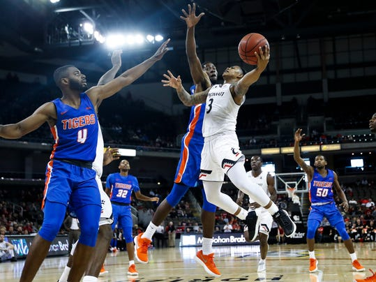 Cincinnati's Justin Jenifer (3) scores against Savannah State's Maricus Glenn, center left, in the second half of an NCAA college basketball game, Friday, Nov. 10, 2017, at BB&T Arena in Newport, Ky. Cincinnati won 107-77. (AP Photo/John Minchillo)