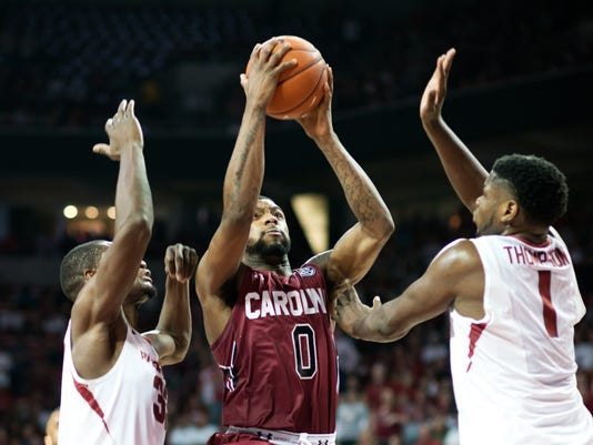 South Carolina's Sindarius Thornwell (0) shoots a basket over Arkansas' Moses Kingsley (33), left, and Trey Thompson (1), right, in the second half of an NCAA college basketball game in Fayetteville, Ark., Saturday, March 5, 2016. South Carolina won 76-61. (AP Photo/Sarah Bentham)