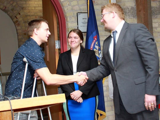 Cameron Cichosz of Howell with Dr. Ryan Keating and Dr. Lauren Azevedo. The doctors were honored at the Barry County Commissioners meeting July 10 for saving the life of Cichosz, whose leg was severed in a boating accident on Gun Lake.