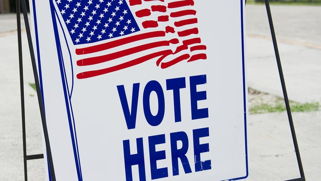 """A """"Vote Here"""" sign is seen outside a polling place"""