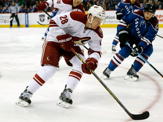 Phoenix Coyotes left wing Lauri Korpikoski, front, of Finland, drives to the net for a shot as Colorado Avalanche defenseman Nick Holden pursues in the first period of an NHL hockey game Monday, Feb. 16, 2015, in Denver. (AP Photo/David Zalubowski)