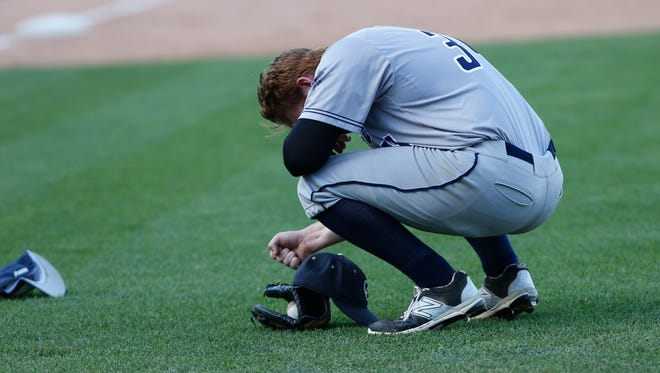 Central Catholic relief pitcher Noah Richardson hangs his head and pounds his fist on the turf after Providence scored on a squeeze bunt with the bases loaded in the bottom of the seventh inning to win the Class 2A State Championship 7-6 Saturday, June 18, 2016, at Victory Field in Indianapolis.