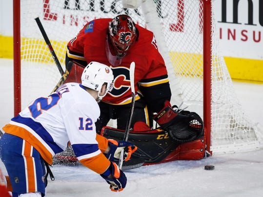 New York Islanders' Josh Bailey has his shot blocked by Calgary Flames goalie Mike Smith during first period NHL hockey action in Calgary, Alberta, Sunday, March 11, 2018. (Jeff McIntosh/The Canadian Press via AP)