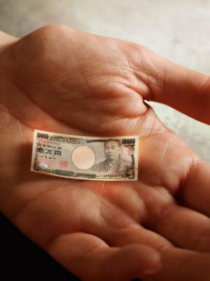 Man's hand holding tiny Yen