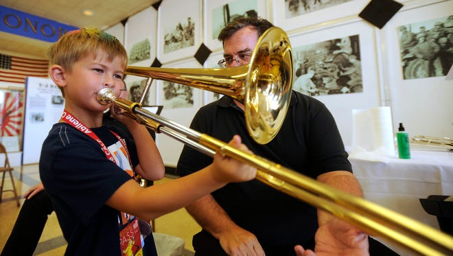 Cason Wilkinson, 6, from Austin, tests out his musical skills as Hardin-Simmons University music professor Jeff Cottrell watches during the Instrument Petting Zoo, part of the Children's Art & Literacy Festival on Friday, June 9, 2017, at the 12th Armored Division Memorial Museum.