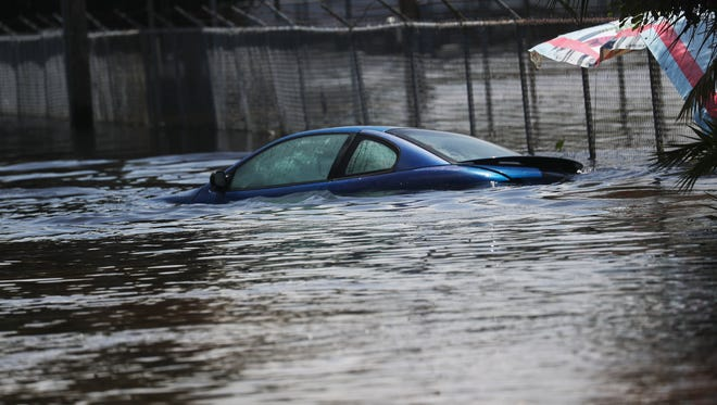 The roof of a submerged car peeks over flood waters near the intersection of Old U.S. 41 and the Tamiami Trail on Tuesday.