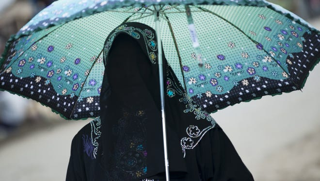 This photo taken on May 21, 2015 shows an ethnic Rohingya Muslim woman holding an umbrella at a camp set up outside the city of Sittwe in Myanmar's Rakhine state.