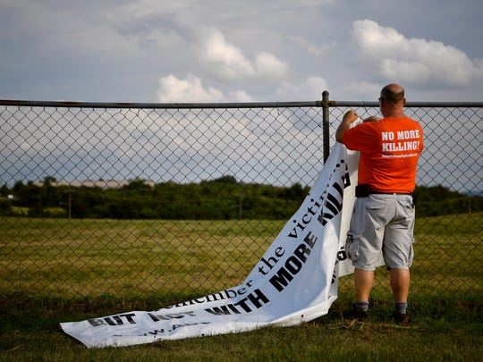 Abraham Bonowitz of Columbus, Ohio, hangs a sign as protesters gather outside the Riverbend Maximum Security Institution against the execution of Billy Ray Irick in Nashville, Tenn., Thursday, Aug. 9, 2018. Irick, 59, was convicted in 1986 on charges of raping and murdering Paula Dyer, a 7-year-old Knox County girl.