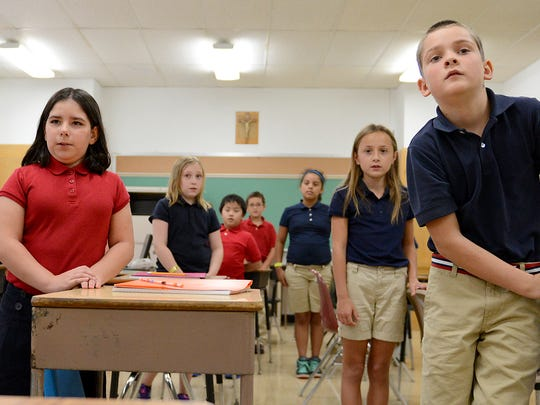 Fourth-grade students recite the school motto in Julie Kreuser's Spanish class at St. Thomas More School on Tuesday.