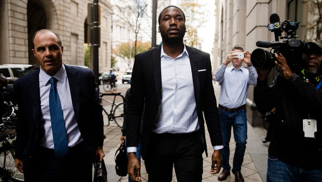 Rapper Meek Mill, center, accompanied by his defense attorney Brian Mcmonagle arrives at the criminal justice center in Philadelphia, Monday, Nov. 6, 2017. A Philadelphia judge has sentenced rapper Mill to two to four years in state prison for violating probation in a nearly decade-old gun and drug case.