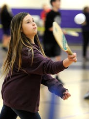 Eighth grader Katelyn Martin returns a ball while playing