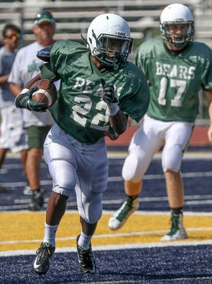 East Brunswick's Kyle Wiggins carries against Colonia in a scrimmage.