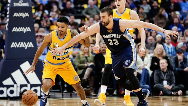 Denver Nuggets guard Gary Harris (14) and Memphis Grizzlies center Marc Gasol (33) battle for a loose ball in the second quarter at the Pepsi Center Sunday.