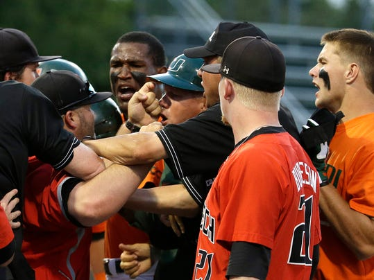 Miami assistant coach Gino DiMare, fourth from right, argues with a Texas Tech coach, second from left, as they are restrained by umpires after David Thompson, right, was out at first in the third inning during an NCAA college baseball regional tournament in Coral Gables, Fla., Sunday, June 1, 2014. (AP Photo/Lynne Sladky)