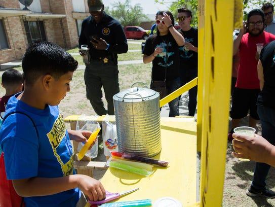 Angel Reyes,9, cuts open popsicles at his lemonade