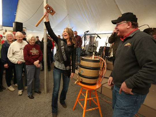 Miss Wisconsin, Raeanna Johnson of Holmen, holds up the copper mallet she used to tap the ceremonial keg of bock beer during Bock Fest at Bull Falls Brewery in Wausau, Saturday, March 21, 2015. At right is Mike Zamzow, one of the brewery's owners.