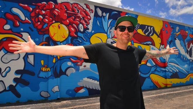 "Los Angeles ""deconstructive pop artist"" Matt Gondek stands in front of his 100-foot mural facing Eau Gallie Boulevard."