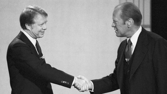 President Gerald Ford, right, and Jimmy Carter shake hands before their debate at the Palace of Fine Arts Theatre on Oct. 6, 1976, San Francisco.