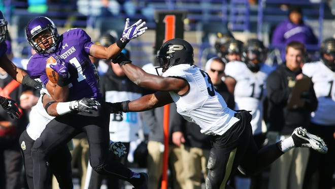 Northwestern Wildcats running back Justin Jackson (21) is tackled by Purdue Boilermakers linebacker Danny Ezechukwu (36) during the first half of the game at Ryan Field.