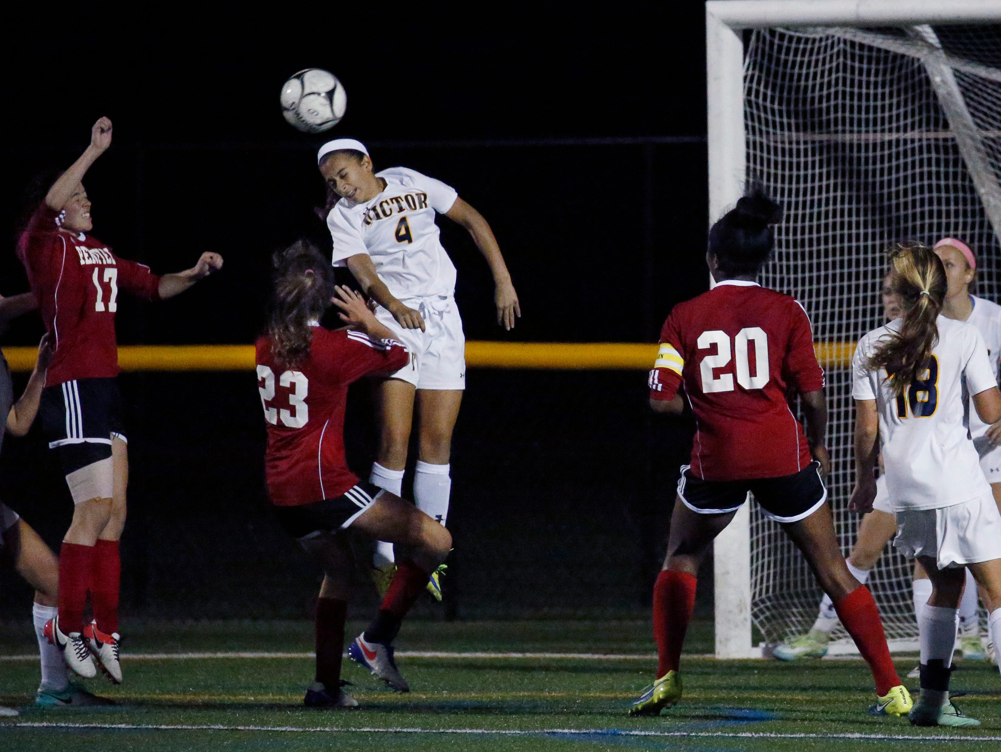 Victor's Olivia Damico jumps for the ball over Penfield players to defend the goal in the first half at Webster Schroeder High School.