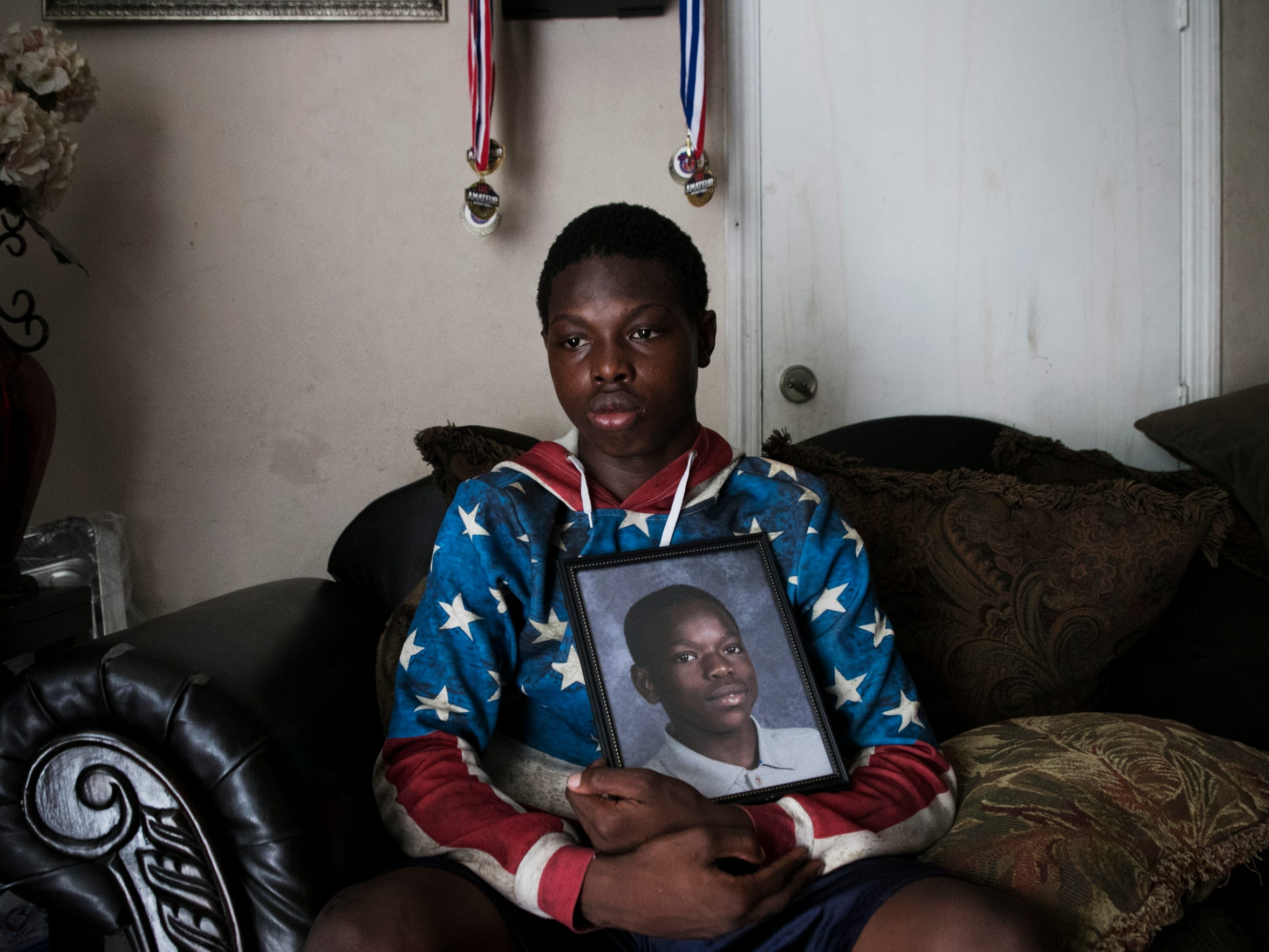 Dsean Archilles,16, holds a photo of his brother Sean