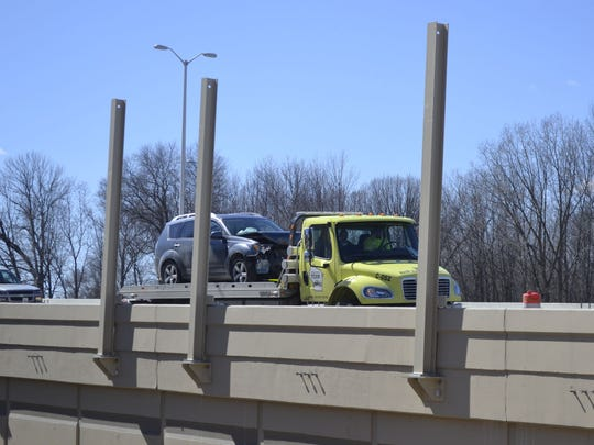 A Wisconsin Department of Transportation Freeway Service Team tow truck hauls away a damaged car involved in a multi-vehicle accident on U.S. 41 northbound south of Mason Street in Green Bay on Saturday, March 28.
