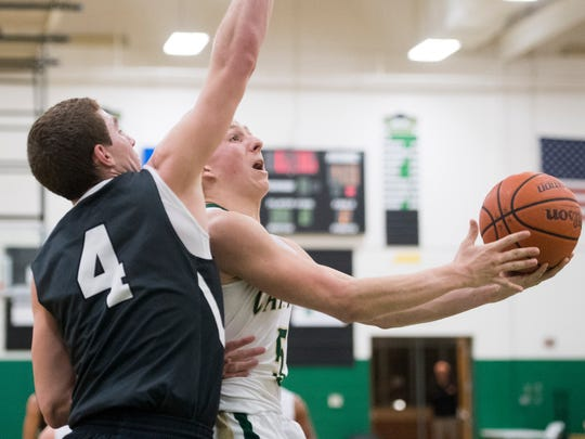 Knoxville Catholic's Jack Sompayrac attempts to score while defended by Jake Giles in the boys basketball game on Monday, January 29, 2018.