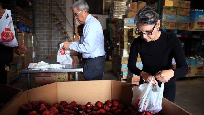 Robert Cuevas (left), board president of the Coastal Bend Food Bank, and Rebecca Martinez bag apples following the unveiling of the new namefor the food bank on Wednesday, September 6, 2017. The name greater reflects the community they serve, which is several counties.