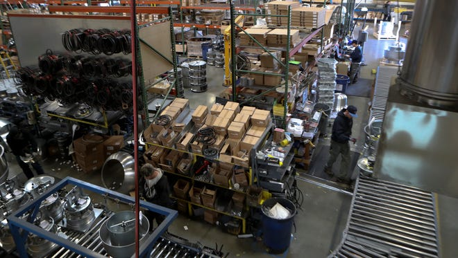 Workers assemble and make fan and ventilator parts Monday at CaptiveAir in Redding. The company is expanding their operation by adding a 34,000 square feet warehouse and office space.