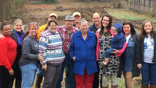 The group of volunteers who have helped Patsy, center, with blue coat, and her daughter Martha, left of Patsy,  secure a lot and build a new home.