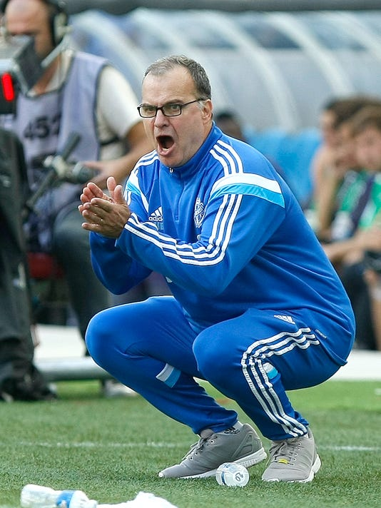 Marseille's Argentinian coach Marcelo Bielsa cheers on his team during their League One soccer match  against Toulouse, at the Velodrome Stadium, in Marseille, southern France, Sunday, Oct. 19, 2014. (AP Photo/Claude Paris)