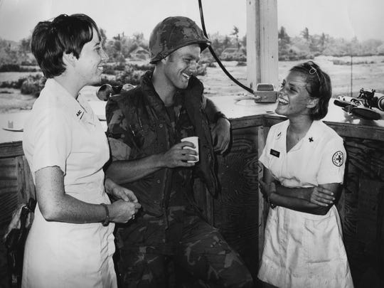 Left, Linda Sullivan Schulte of Westminster, Maryland, and Dorset Hoogland Anderson of Cummington, Massachusetts, talk with a soldier (name unknown) in July 1969 in Vietnam.
