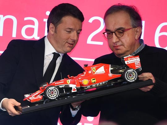 Italian prime minister Matteo Renzi, left, and President of Ferrari Sergio Marchionne, hold a F1 car model at the stock exchange as the Ferrari luxury carmaker made its Milan stock market debut, in Milan, Italy, Jan. 4 2016. The company famed for its Formula 1 racing machines and coveted red roadsters began trading Monday morning, the first business day of the year, at 43 euros ($47) under the RACE ticker.