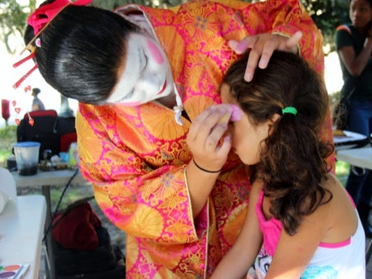 A child gets her face painted in traditional Japanese performance makeup