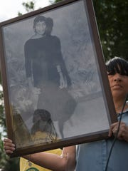 Pamela Spellman holds a photograph of her mother, Eloise Spellman, who was shot and killed during the upheaval.