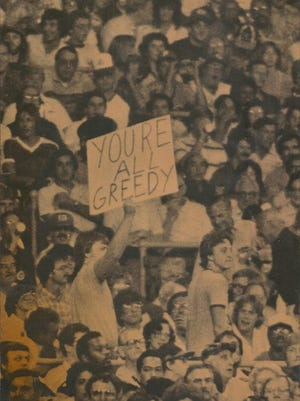 """Perry Township's Jerry Harter carries a sign reading, """"YOU'RE ALL GREEDY,"""" during the 1981 All-Star Game in Cleveland."""